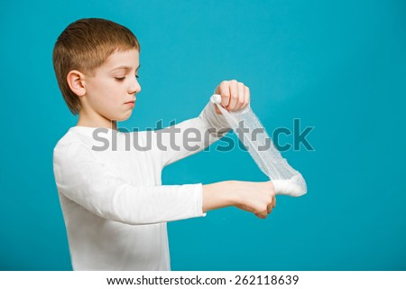 Boy in white clothes taping up bandage on his thumb - stock photo