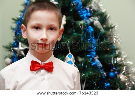 boy in white shirt and red bow tie standing near Christmas tree - stock photo