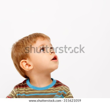 Boy in winter clothes looking up on white background - stock photo
