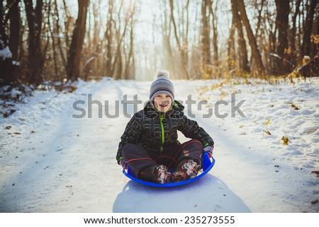 Boy in winter outdoors sledding - stock photo