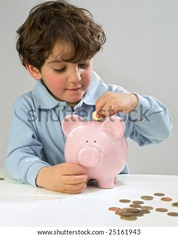 boy inserting a coin to a piggy bank - stock photo