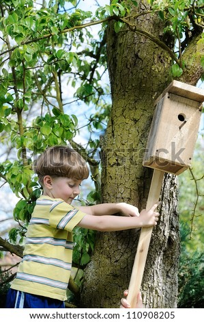 Boy installing a self-made Bird House.