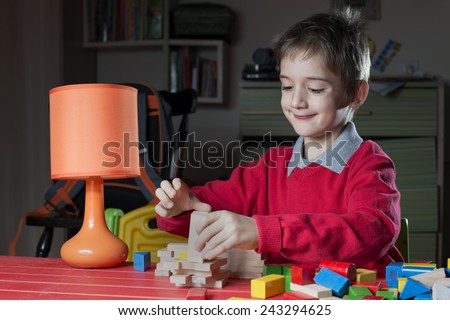 boy is arranging wooden toy constructor  - stock photo