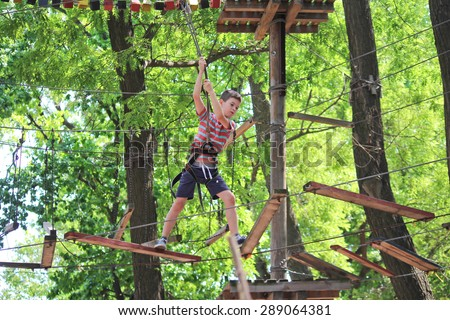 Boy is climbing in rope attraction park