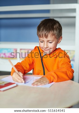 Boy is drawing with pencils. Boy in bright orange pullover. home activity. Boy is carefully drawing a picture.