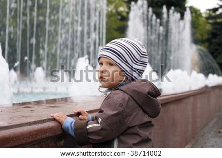boy is dressed in warm clothes on a walk in a park