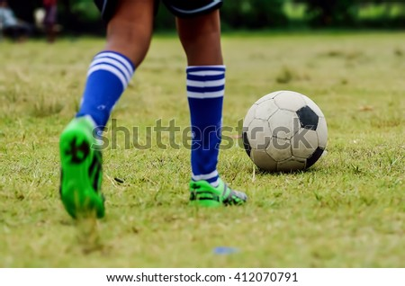 Boy is going to kick soccer ball. - stock photo