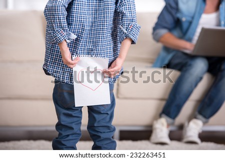 Boy is holding a paper with a picture of heart, against the background of a man sitting with a laptop. - stock photo