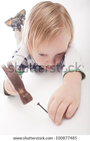 boy is looking at hammer and nail, partly isolated