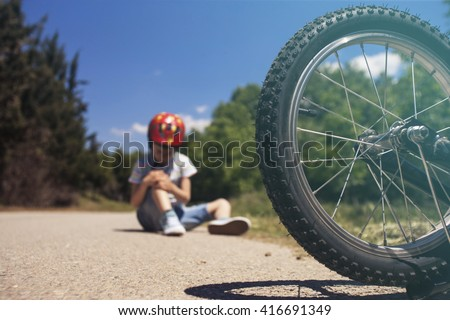 Boy is lying hurt after a bicycle accident. Kids safety concept. Selective focus toned image with shallow depth of field - stock photo