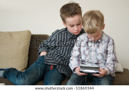 Boy is playing on his portable computer and his brother likes to watch.