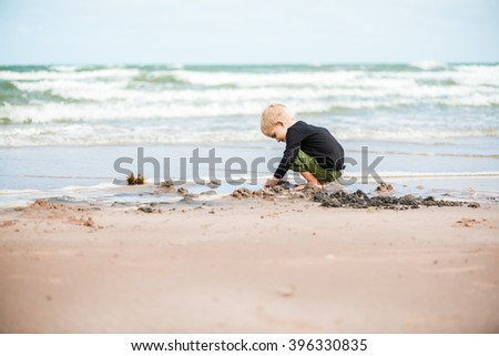 Boy is playing on the beach with sand