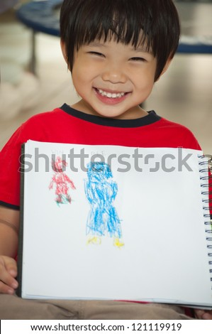 Boy is proudly to present his painting which mom painted in blue and he's red. - stock photo