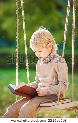 Boy is reading a book outdoors - stock photo