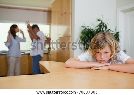 Boy is sad about fighting parents behind him - stock photo