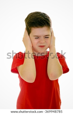 Boy is shutting his ears, ignoring over white background - stock photo