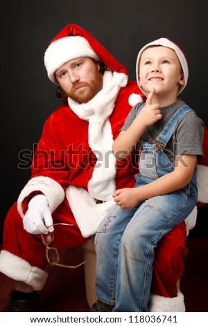Boy is  sitting on Santas knee and thinking about his future present.  Man,dressed in Santa costume looks tired and unhappy