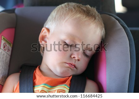 Boy is sleeping in a child car seat - stock photo