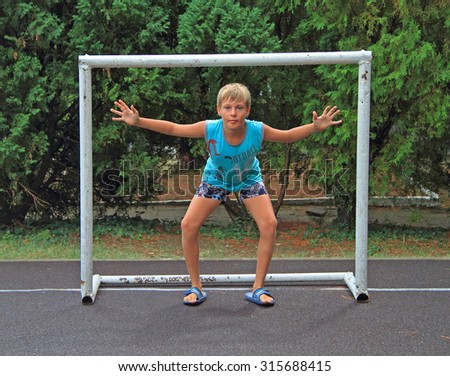 boy is standing in goalkeeper position on play field - stock photo