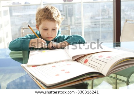 Boy is studying at home with mom