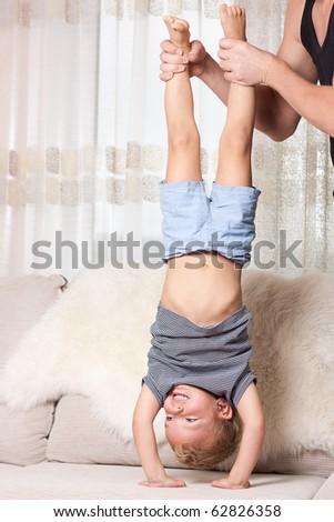 Boy is upside down, indoor. - stock photo