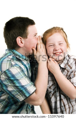 boy is whispering in girls ear