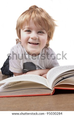 Boy isolated againt a white background reading a book and smiling