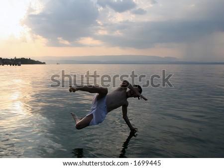 Boy joyfully jumping in the lake - stock photo