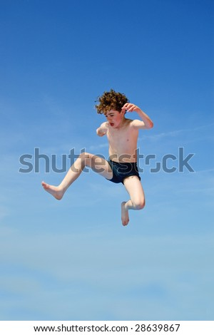 Boy jumping against blue sky