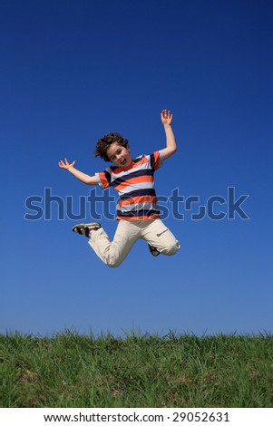 Boy jumping against blue sky - stock photo
