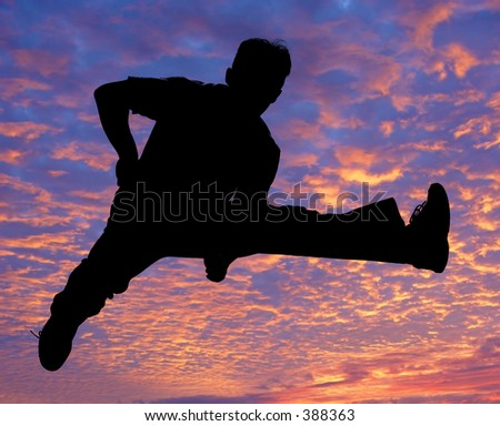Boy jumping against sunset