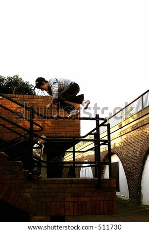 boy jumping down stairs over metal railings - stock photo