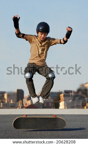 Boy jumping from skateboard wearing protective gear with cityscape in the background