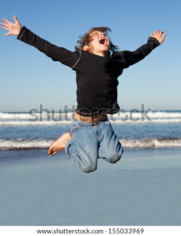 boy jumping high by the ocean