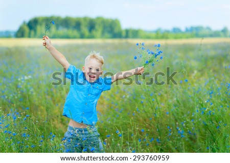 Boy Jumping In A Filed Of Wild Flowers - stock photo
