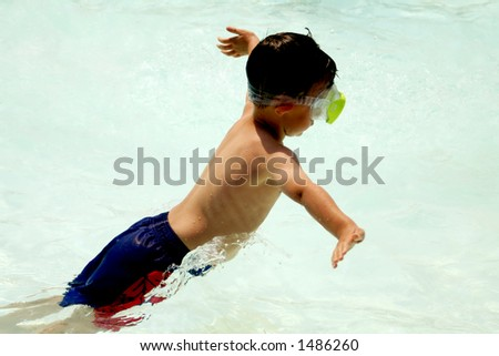 Boy jumping in pool - stock photo