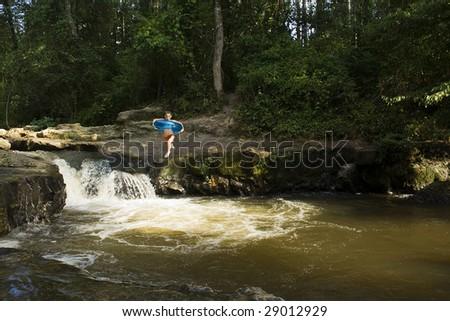 Boy jumping into water below a waterfall - stock photo
