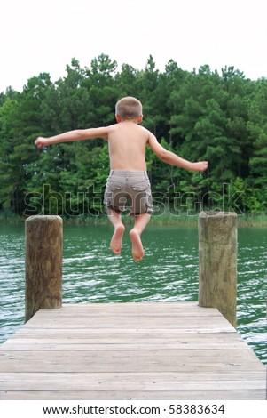 boy jumping off dock - stock photo