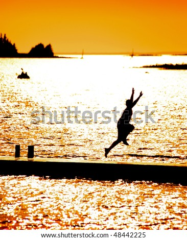Boy Jumping Off Dock On Sunny Afternoon - stock photo