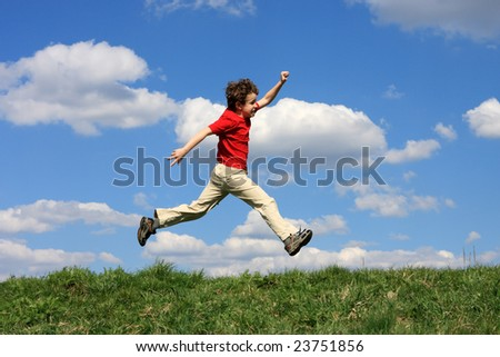 Boy jumping on green meadow against blue sky
