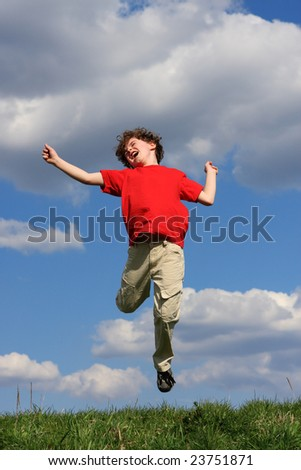 Boy jumping on green meadow against blue sky - stock photo