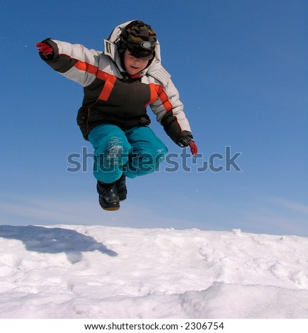 Boy jumping over snow on blue sky