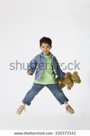 Boy jumping while holding teddy bear - stock photo