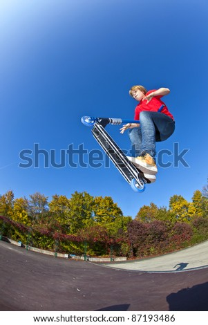 boy jumping with his scooter at the skate park under blue clear sky