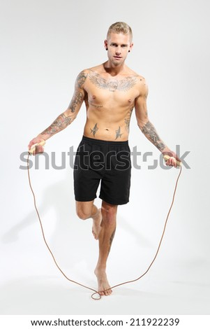 Boy jumps rope . Attractive young boy jumping rope, tattooed in sports trousers  - stock photo