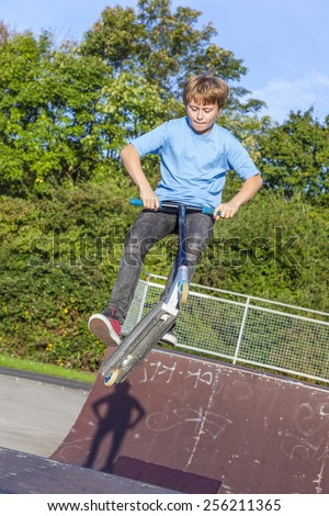 boy jumps with scooter at the skate park over a ramp and has fun - stock photo