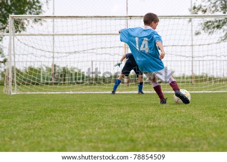 boy kicking a penalty at goal - stock photo