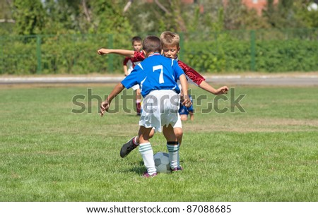 boy kicking football on the sports field - stock photo