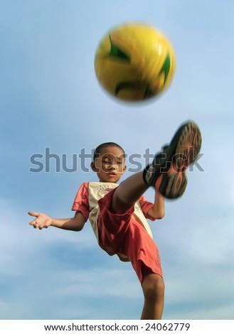 Boy kicks the ball - stock photo