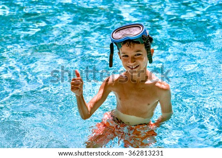 Boy kid child eight years old inside swimming pool portrait happy fun bright day diving goggles